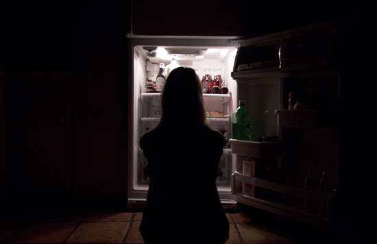 Character Joy sits in front of a fridge staring into it while the light glows around her